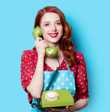 Girl in red dress with green dial phone Stock Photos