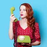 Girl in red dress with green dial phone Royalty Free Stock Photography