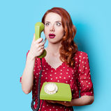 Girl in red dress with green dial phone Stock Photography