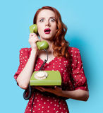 Girl in red dress with green dial phone Stock Images