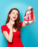 Girl in red dress with gumshoes. Surprised redhead girl in red dress with gumshoes on blue background Royalty Free Stock Image