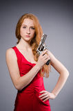 Girl in red dress with handgun against gray Stock Images