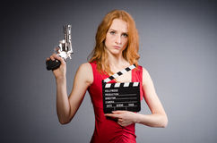 Girl in red dress with handgun and clapperboard Royalty Free Stock Image