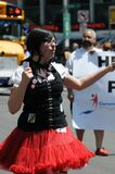 Girl in red dress handing out pamphlets at Gay Pride Parade Royalty Free Stock Photo