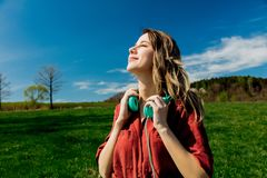Girl in red dress and hat have a carefree time with headphones on meadow royalty free stock images