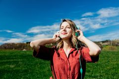 Girl in red dress and hat have a carefree time with headphones on meadow stock photography