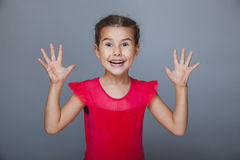 Girl in a red dress held up her hands delight on Royalty Free Stock Image