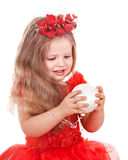 Girl in red dress holding christmas ball. Stock Image