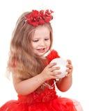 Girl in red dress holding christmas ball. Stock Image