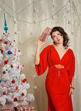 Girl in red dress holding gift near Christmas tree. Royalty Free Stock Image