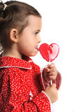 Girl in a red dress holding a lollipop Stock Images