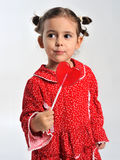 Girl in a red dress holding a lollipop Royalty Free Stock Photography