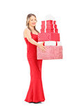 Girl in red dress holding a pile of presents Royalty Free Stock Photography