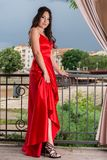 Girl in red dress holding dress and showing her leg and shoes on the garden balcony. Beautiful woman in red dress holding dress and showing her leg and shoes on stock photos