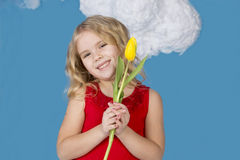 Girl in a red dress holding a yellow tulip Royalty Free Stock Photography