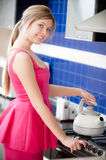 Girl in red dress holds teapot Stock Image