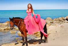 The girl in red dress on horsе. A portrait of a caucasian girl with her horse Royalty Free Stock Photos