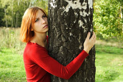 Girl in red dress hug a tree, looking at side Stock Photos