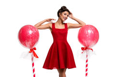 Girl in red dress with huge lollipops Stock Images