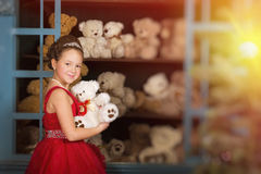 Girl in a red dress hugging a teddy bear Stock Photos
