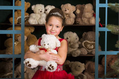Girl in a red dress hugging a teddy bear Stock Images