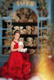 Girl in a red dress hugging a teddy bear Stock Photo