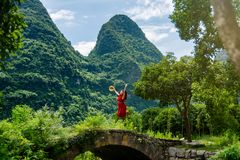 Girl in red dress jumping on the old stone bridge. In Yangshuo royalty free stock photography
