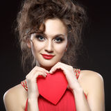 Girl in red dress keeps the heart. Concept of Valentine's Day Royalty Free Stock Photography