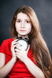 Girl in red dress late with alarm clock Stock Image
