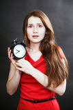 Girl in red dress late with alarm clock Stock Images