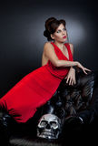Girl red dress with leather chair and skull Royalty Free Stock Image