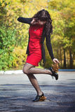The girl in a red dress with leaves on heels. In the park Stock Photo