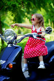Girl in a red dress on a motorcycle. Beautiful little girl in a red dress on a motorcycle Royalty Free Stock Image