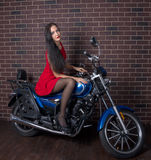 Girl in red dress on a motorcycle Royalty Free Stock Photos