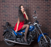 Girl in red dress on a motorcycle Stock Image
