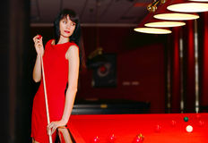Girl in red dress playing a billiards. Stock Photography
