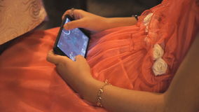 Girl in a red dress playing a game on a phone. Girl in a red dress playing a game on smart phone in cafe stock video footage
