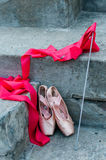 The girl in red dress and pointe. Red ballet shoes and a ribbon on a gray background Royalty Free Stock Photos