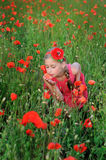 Girl in a red dress on the poppy field smelling a flowers Royalty Free Stock Photos