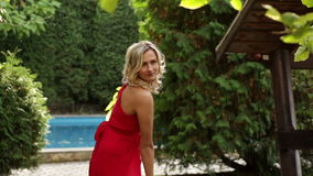Girl in red dress posing in the park.  stock footage