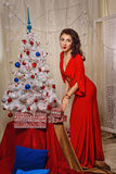 Girl in red dress puts gifts near Christmas tree. Royalty Free Stock Photos