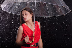 Girl in a red dress in the rain Royalty Free Stock Images