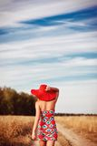 Girl in red dress with red hat on the field Royalty Free Stock Image
