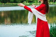 Girl in a red dress by the river 2 stock images