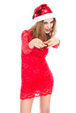 Girl in red dress and santa hat pointing finger at camera Royalty Free Stock Image