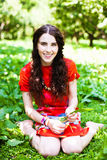 Girl in red dress seating in the grass Stock Images