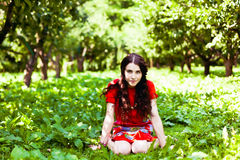 Girl in red dress seating in the grass Royalty Free Stock Photo