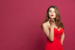 Girl in a red dress sending a kiss Royalty Free Stock Photos