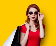 Girl in red dress with shopping bags Stock Photography