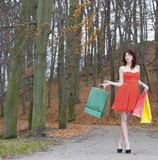 Girl in red dress with shopping bags walking in park Royalty Free Stock Image